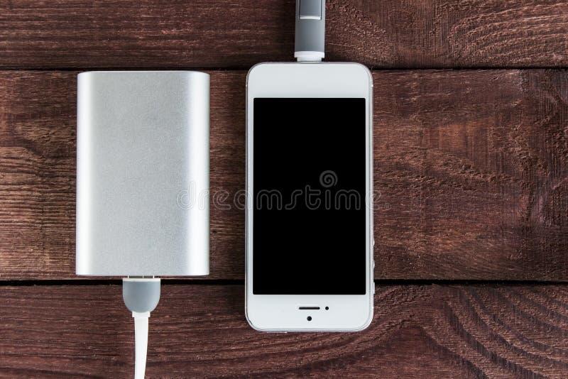 Laddande Smartphone med Powerbank på en träbakgrund port royaltyfria bilder