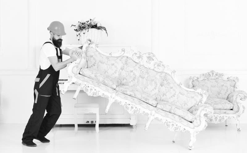 Laddaren flyttar soffan, soffa Kuriren levererar möblemang i fall att av flyttar sig ut, förflyttning Hemsändningbegrepp royaltyfri foto