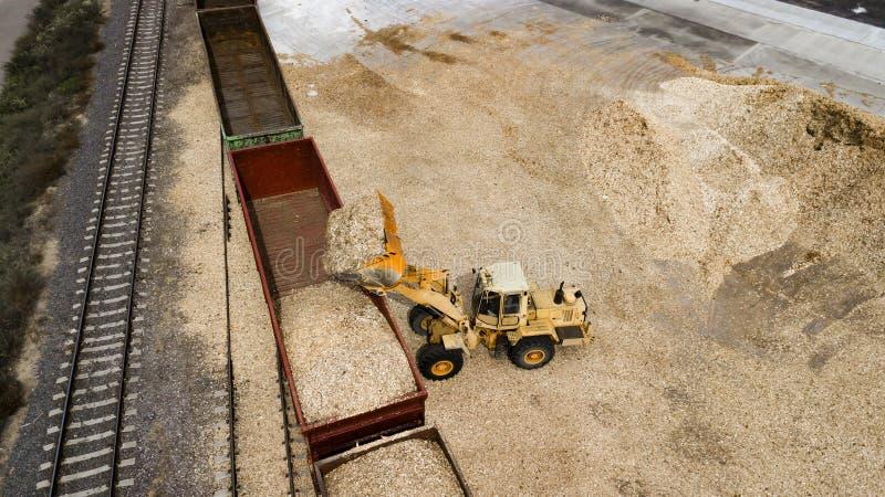 Laddaren laddar sågspånet i den flyg- sikten för snickerifabriken arkivfoton