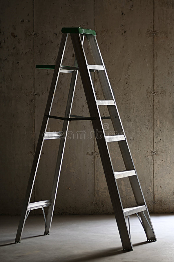 Ladder in Basement. Aluminum ladder in a dark basement with dirty cement walls and floor stock image