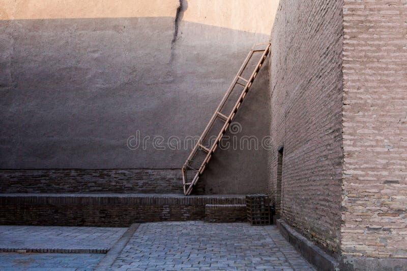 Ladder and brick walls. In Itchan Kala, the ancient inner city part of Khiva, Khorezm Region, Uzbekistan royalty free stock photo