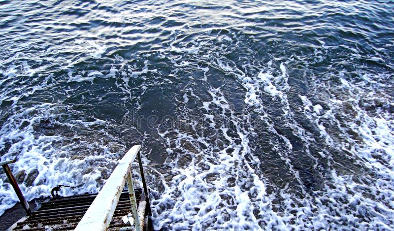 Ladder descent into the bubbling water of the winter sea, Baltic sea in wintertime. Ladder descent into the bubbling water of the winter sea. Baltic sea in stock photos