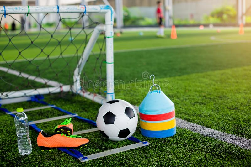Ladder drills, goal, soccer ball, marker cones, sports shoes and bottle water on green artificial turf. For soccer training equipment stock photos