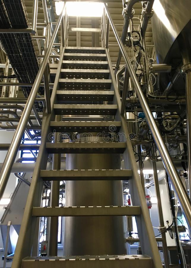 Ladder Inside Brewery. A tall ladder reaches to the top level inside a brewery amid stainless steel equipment royalty free stock photo