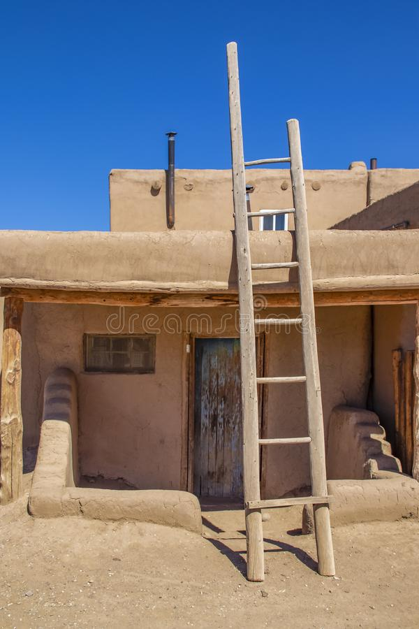 Ladder leading to second story apartments on traditional mud adobe pueblo with porch and old grunge wooden door in American stock photos