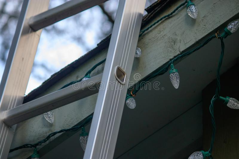 Ladder leaning up on roof to decorate for christmas royalty free stock image