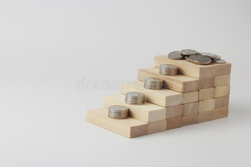 Ladder made of wooden bricks on which coins lie, Ukrainian hryvnia. Concept of money growth, profit and capital accumulation. Isolated Open Space stock photos