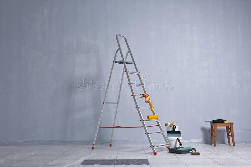 Ladder, paint and tools for making repair stock image