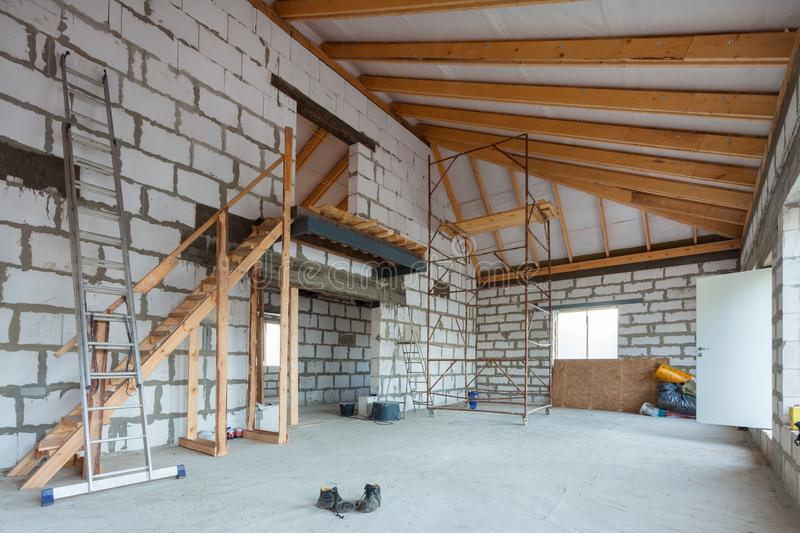 Ladder, parts of scaffolding and construction material on the floor during on the remodeling, renovation, extension, restoration stock photo