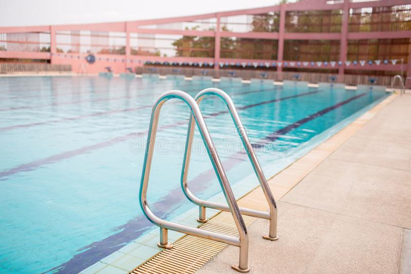 Ladder stainless handrails for descent into swimming pool. Swimming pool with handrail. stock photos