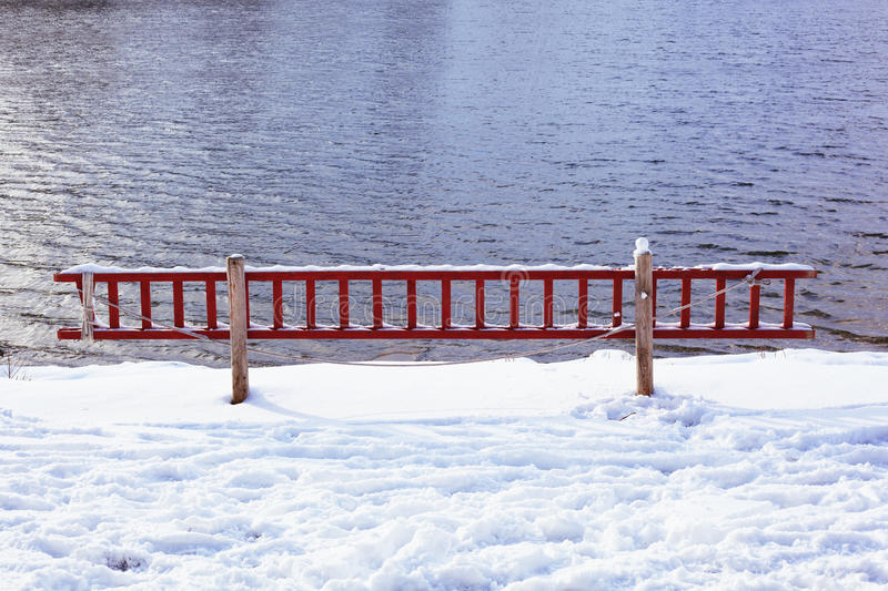 Ladder to rescue in frozen lake stock photography