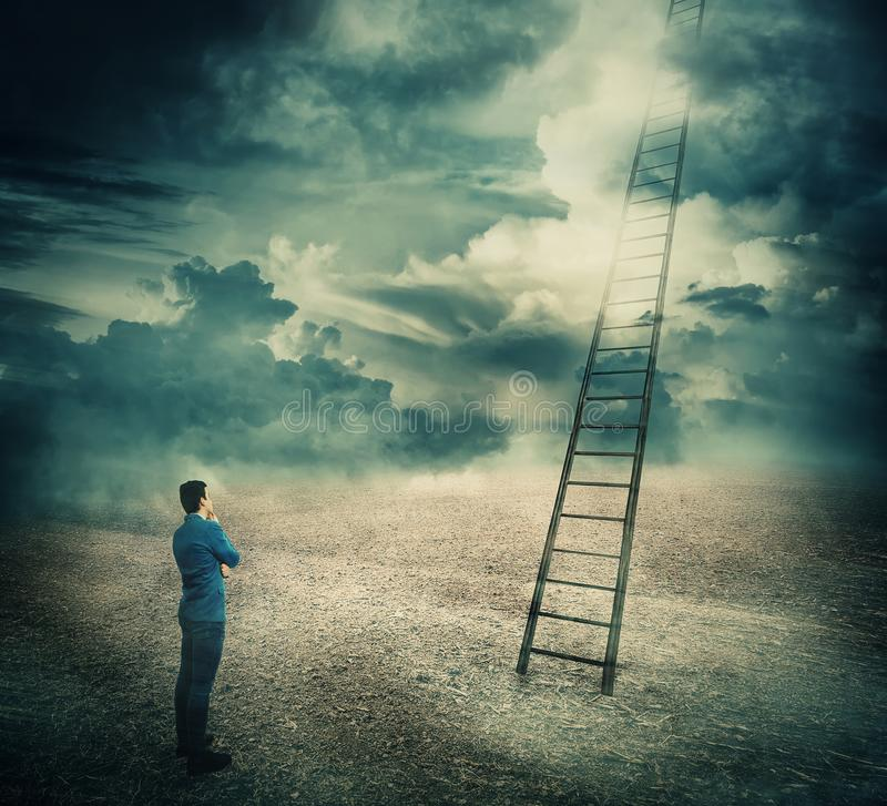 Ladder to unknown. Surreal view of a businessman thoughtful looking at a huge ladder going up in the sky reaching the clouds. Stairway to unknown paradise stock photography