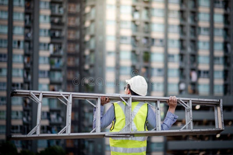 Ladder van het de mensen de dragende aluminium van de onderhoudsarbeider royalty-vrije stock foto