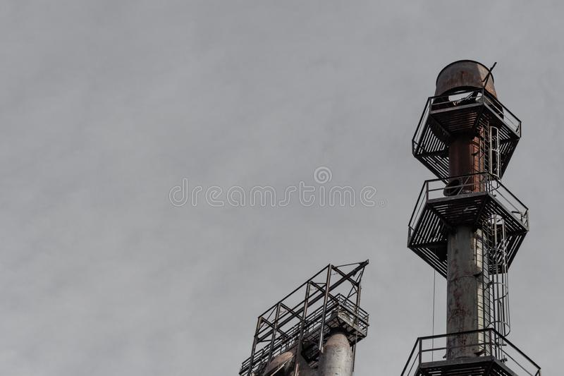 Ladders and walkways encircling an exhaust stack in an industrial complex silhouetted against gray sky, copy space stock photo