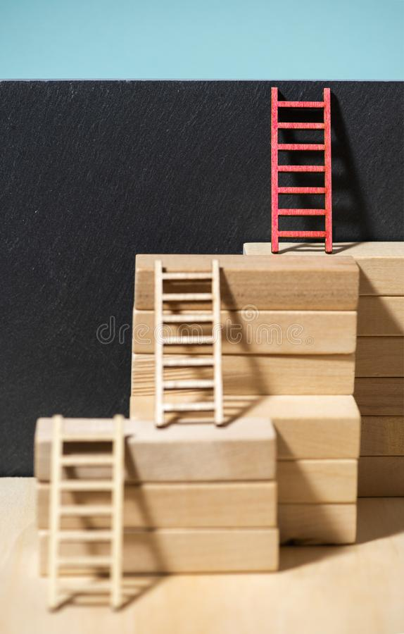 Ladders on the wall. Concept for success and growth. Stairs made of wooden blocks. Blue wall stock image