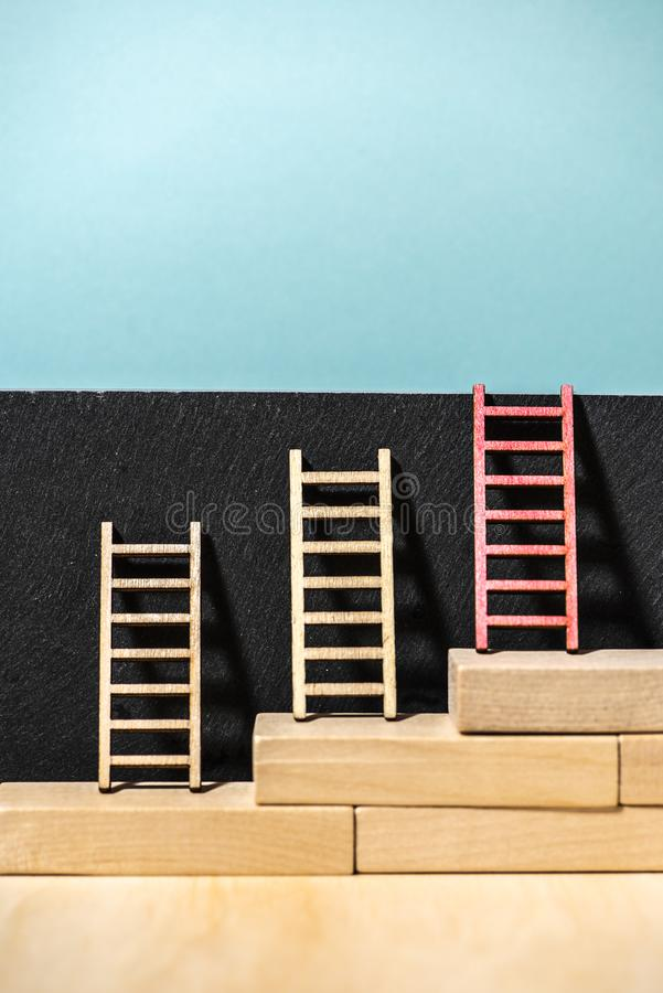 Ladders on the wall. Concept for success and growth. Stairs made of wooden blocks. Blue wall royalty free stock photography