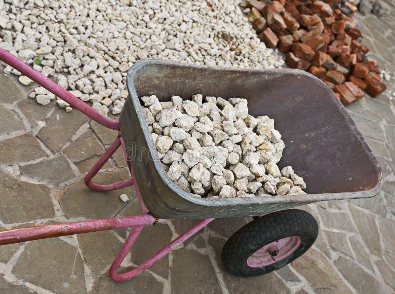 Laden pram av många små stenar arkivfoton