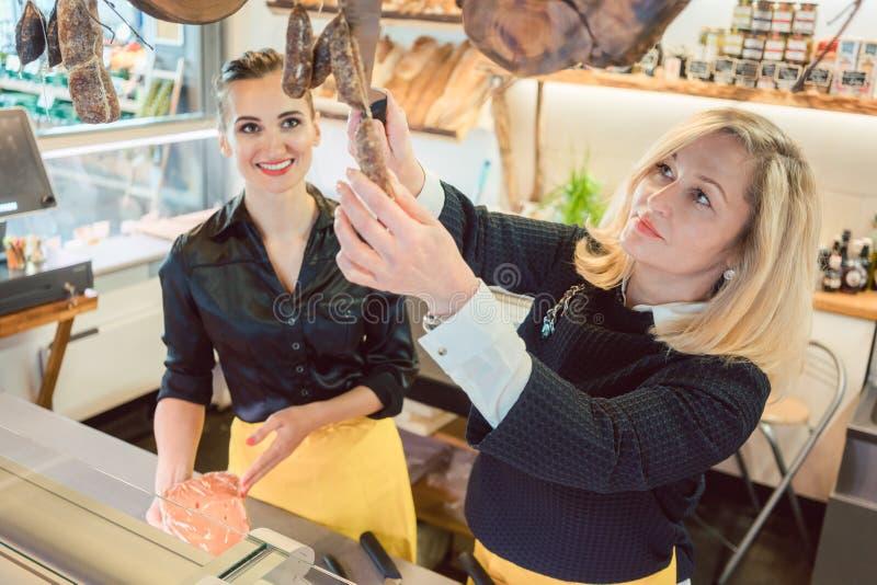 Ladenassistenten - Frauen verkaufen Käse und Fleisch in Deli stockfoto