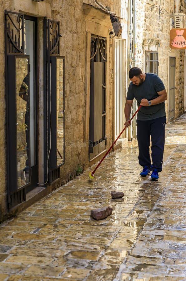 Ladenbesitzer, der die Pflasterstraße durch sein Geschäft in der mittelalterlichen alten Stadt in den Balkan in Budva, Montenegro lizenzfreie stockfotografie