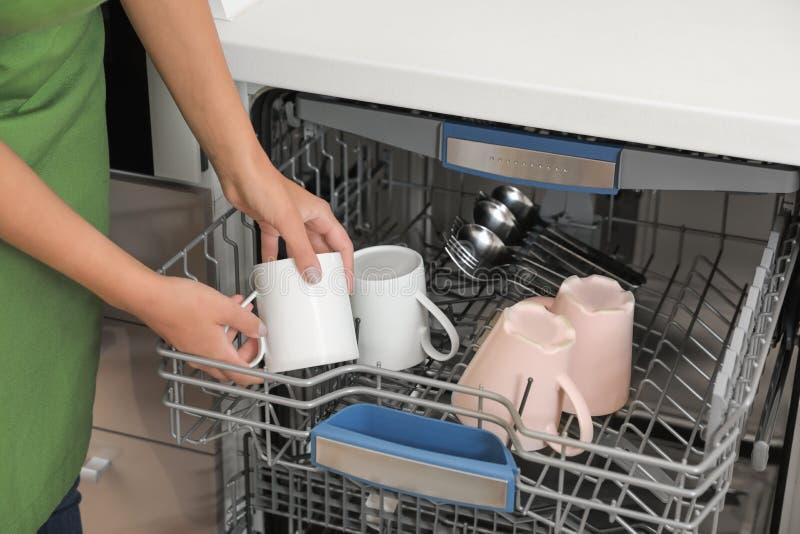 Ladende Spülmaschine der jungen Frau in der Küche stockfoto