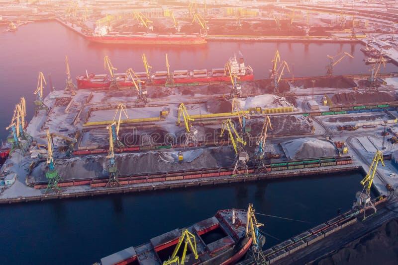 Ladender Kohlenbergbau im Hafen auf Frachttanker mit Kraneimer des Zugs Von der Luftdraufsicht stockbild