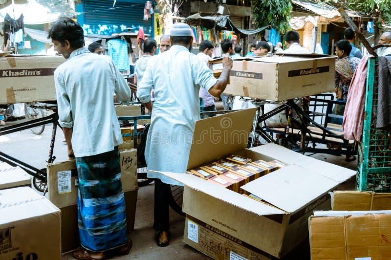 Lader, der Pappbehälter- oder Versandkastenkarikatur entlädt oder auspackt Sammelpacks auf hölzerner Palette auf einem weißen Hin stockfotos