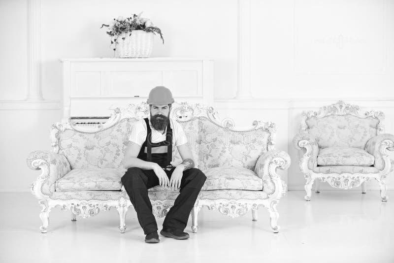 Lader sitzen auf Sofa und haben Ruhepause und Restkonzept Mann mit Bart, Arbeitskraft im Overall und Sturzhelm, der auf Couch sit lizenzfreie stockfotos