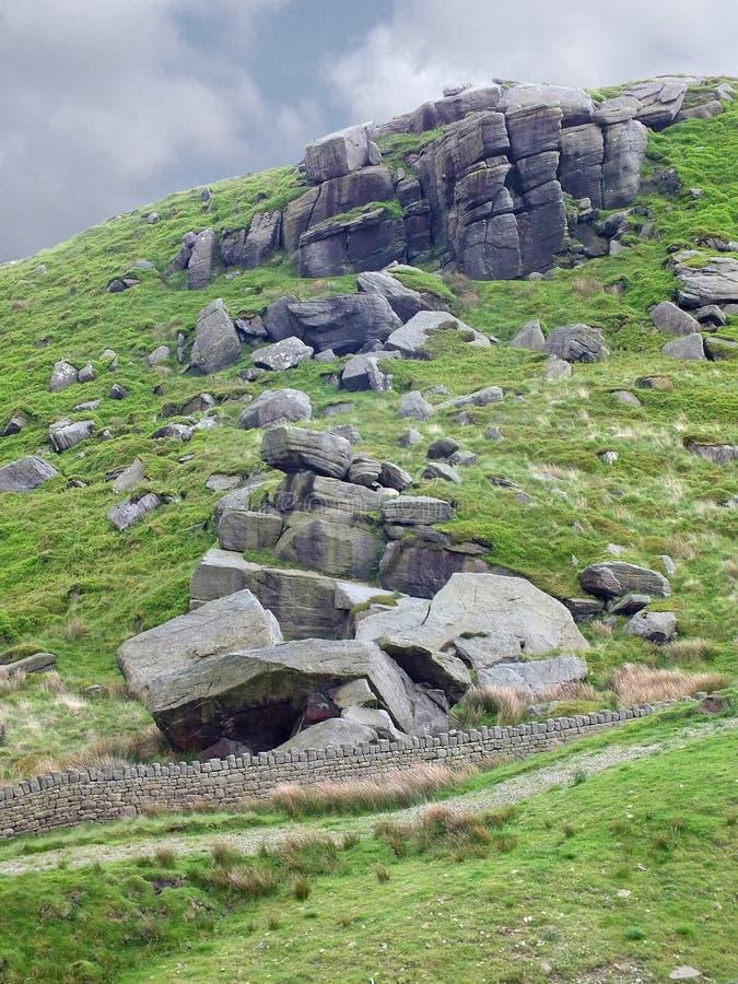Ladera escarpada de los peninos con los cantos rodados dispersados y un afloramiento rocoso grande con una pared de piedra seca y imagen de archivo libre de regalías
