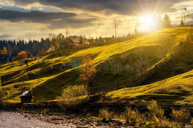 Ladera rural herbosa cerca del pueblo en la puesta del sol foto de archivo