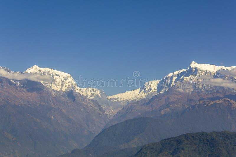 Laderas con los bosques verdes en el fondo de las montañas del desierto y el canto nevoso de Annapurna debajo de un cielo azul cl foto de archivo libre de regalías