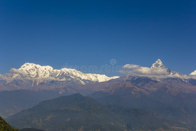 Laderas enselvadas en un valle brumoso de la montaña con los picos nevosos del Annapurna Ridge con las nubes blancas debajo de un imágenes de archivo libres de regalías