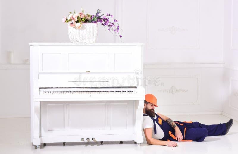 Laderhelling op pianoinstrument Lui arbeidersconcept Mens met baard, arbeider in overall en vermoeid in slaap van de helmdaling stock afbeelding