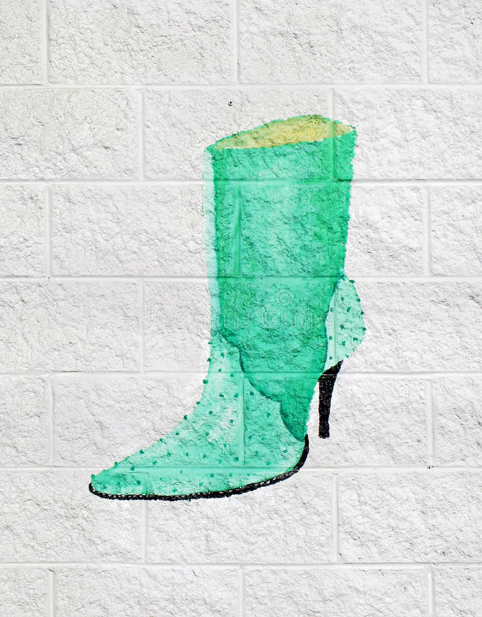 Ladies Bootie Painted on Wall. A ladies ostrich skin bootie painted on a white breeze block wall royalty free stock photo