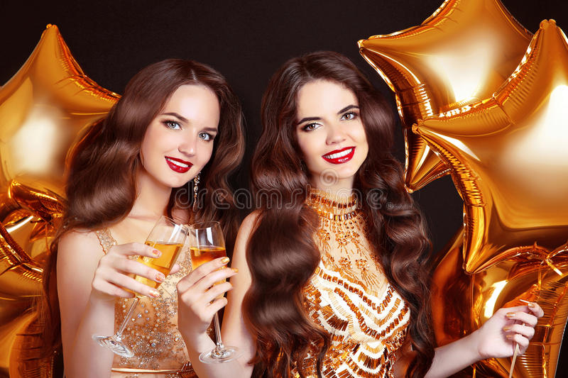 Ladies clinking glasses, party Celebration. Happy women congratulations over golden stars balloons isolated on black background. royalty free stock photos