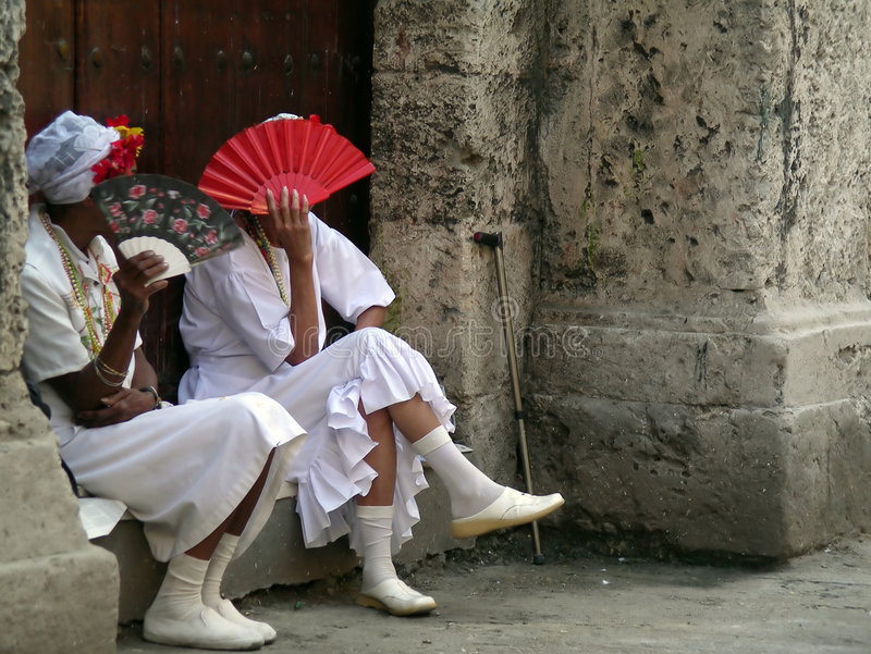 Ladies in cuba. Covering their faces with fans in traditional cuban costumes stock photography