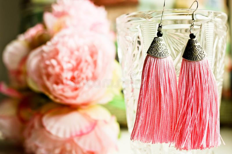 Ladies earrings tassels close up view with beautiful colored background. Famales fashion concept of accessories stock photography