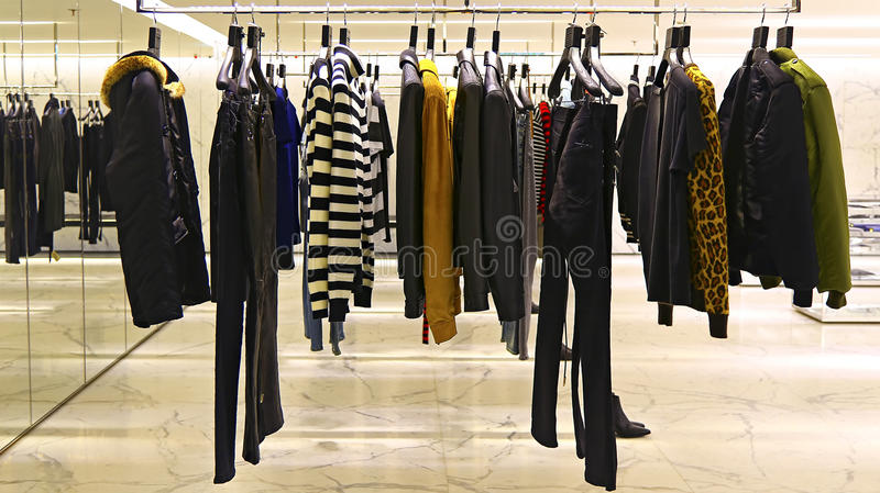 Ladies garments store. Winter fashion clothes for ladies on display on metal racks at a garments store stock photography