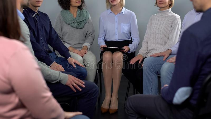 Ladies and men talking with female psychologist, rehabilitation therapy session stock image