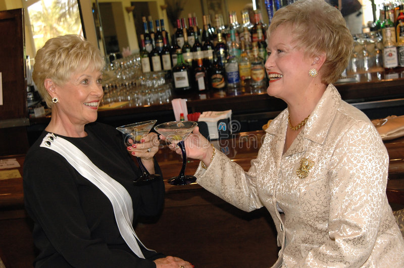 Ladies night out. Two laughing well dressed senior women having drinks in a bar