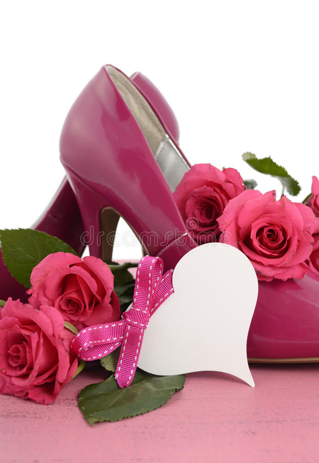 Ladies pink high heel stiletto shoes and roses. International Womens Day, March 8, ladies pink high heel stiletto shoes and roses on vintage pink wood background stock image