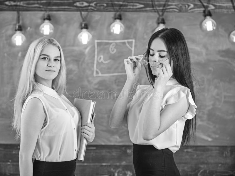 Ladies ready to start private lesson, chalkboard on background. Attractive teachers overworking after classes. Teachers stock photos