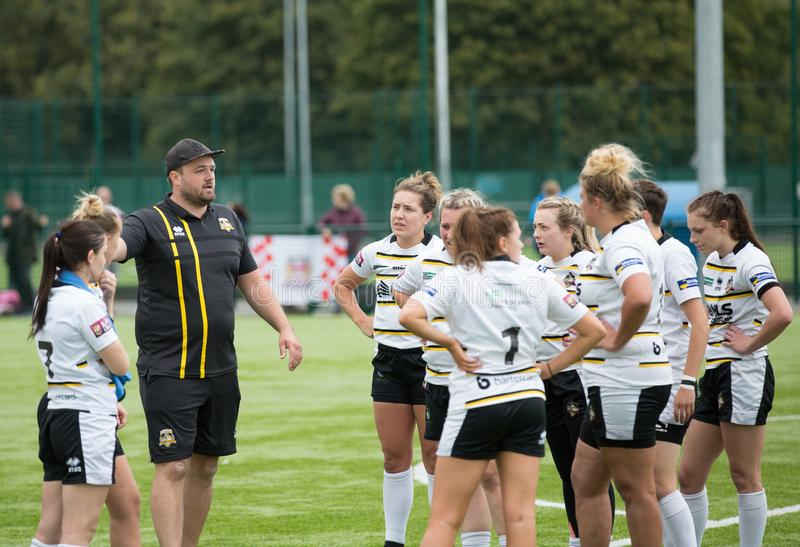 Ladies Rugby League Coach Talking Tactics. The head coach of a ladies rugby league team giving a pep talk and talking tactics at half time during a match royalty free stock image