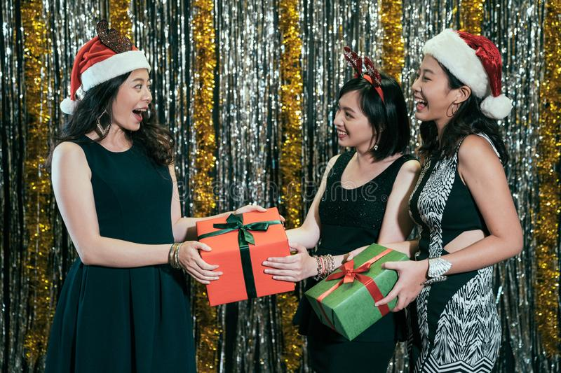 Ladies with santa hats exchange christmas gifts royalty free stock photos