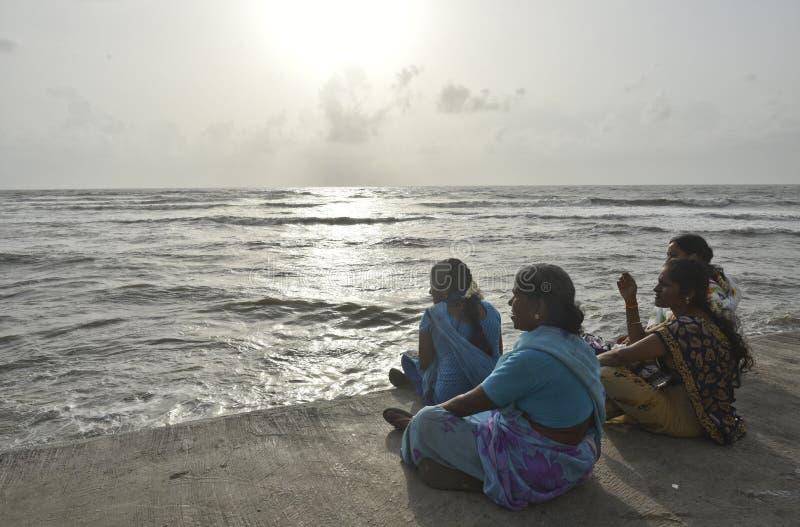 Ladies and the sea. Mumbai, India - 14th June 2016: Rural Indian ladies enjoying the view at Haji Ali Dargah, Mumbai, India, on Tuesday, June 14, 2016 royalty free stock photos