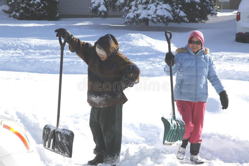 Ladies Shoveling Snow. Ladies with shovels in the deep snow in the driveway after a big snow storm royalty free stock photos