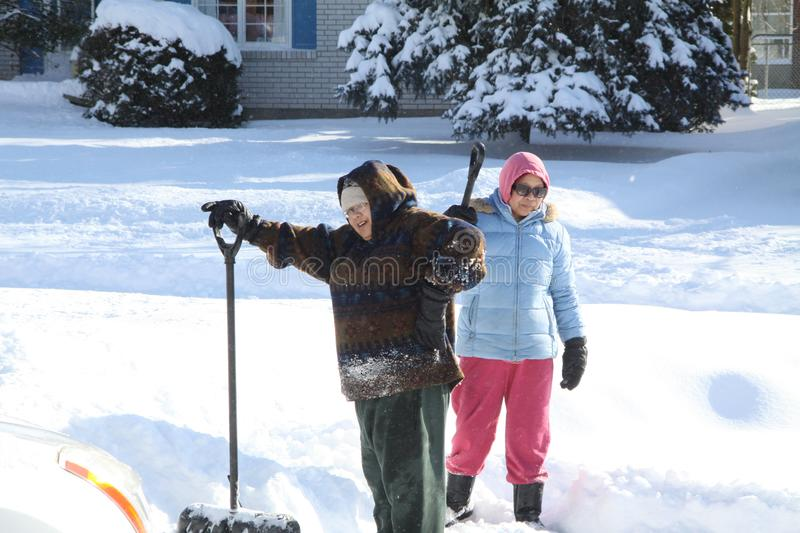 Ladies Shoveling Snow. Ladies with shovels in the deep snow in the driveway after a big snow storm stock photo