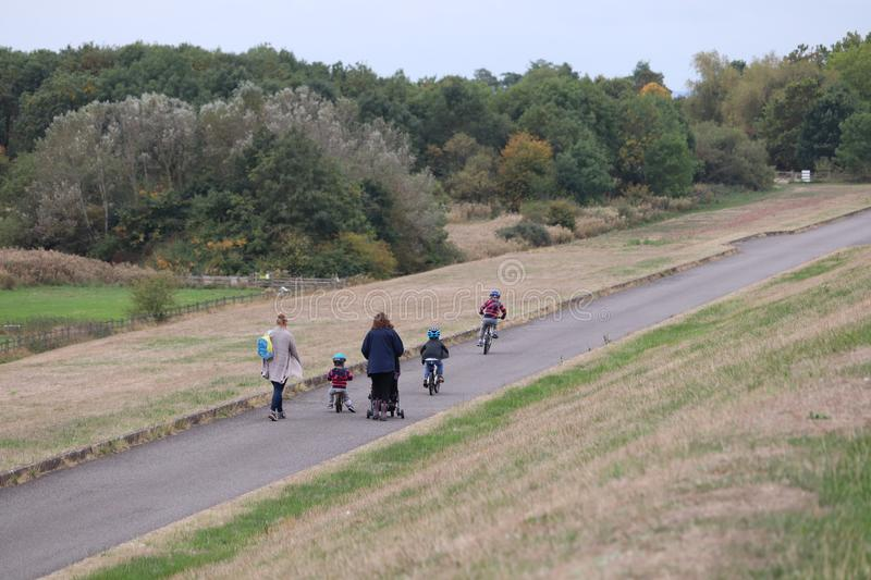 Family of parents and children walking and cycling on a path. Ladies and small children walking around a leisure park. Children happy cycling along with safety stock images