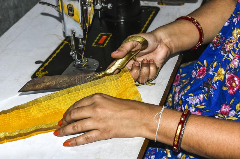 Ladies tailor of India cutting clothes with scissor and making dress by sewing machine royalty free stock images