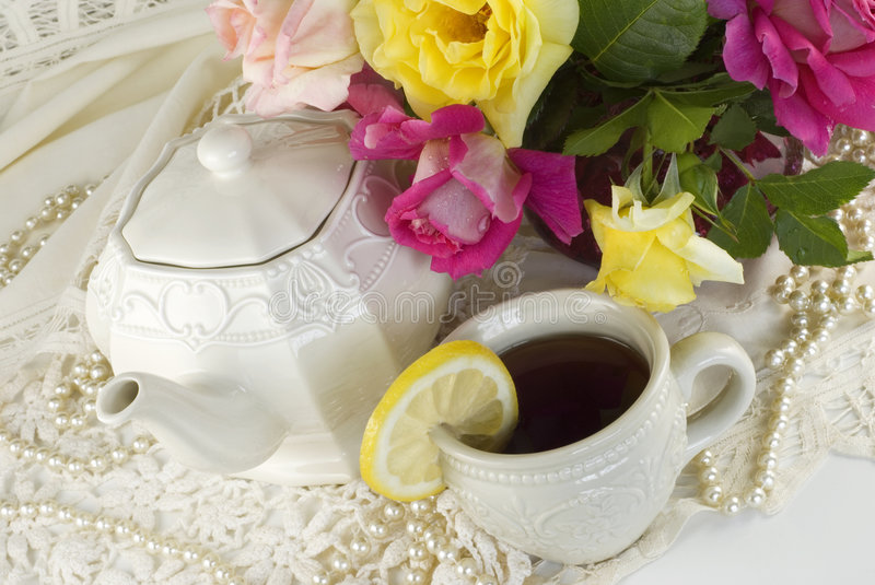 Ladies Tea Party. A ladies tea party decorated with antique lace, pearls and fresh garden roses, horizontal with copy space royalty free stock image