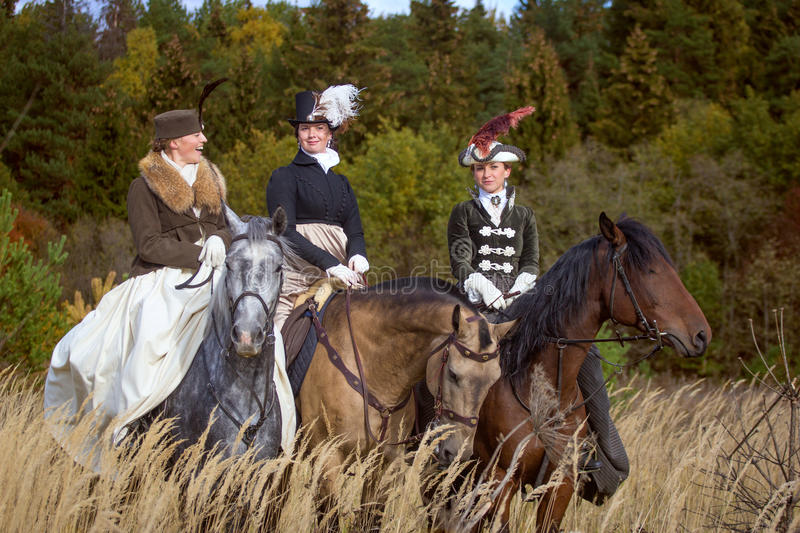 Ladies in 19th century dress riding horses. Young pretty ladies talking while riding horseback in the field. Nineteenth century dress. Autumn hunting with horses royalty free stock images